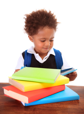 schoolbag: Portrait of sweet little black boy reading books isolated on white background, preparation to go to first class, back to school concept