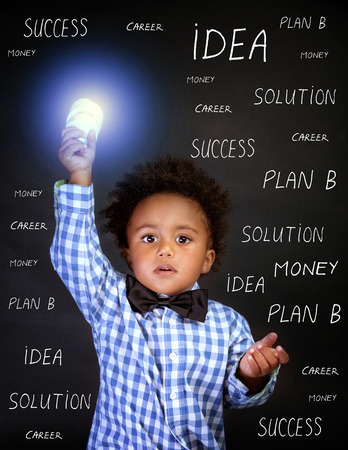 find solution: Portrait of little African genius boy with lightbulb in the hand on blackboard background, back to school, find solution concept