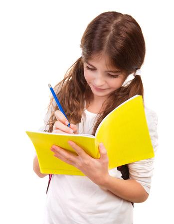 niños escribiendo: Niña de la escuela por escrito en el cuaderno aislado en el fondo blanco