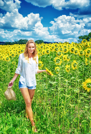 Beautiful young woman walking on fresh sunflowers field, majestic beauty of countryside nature, summer traveling concept photo