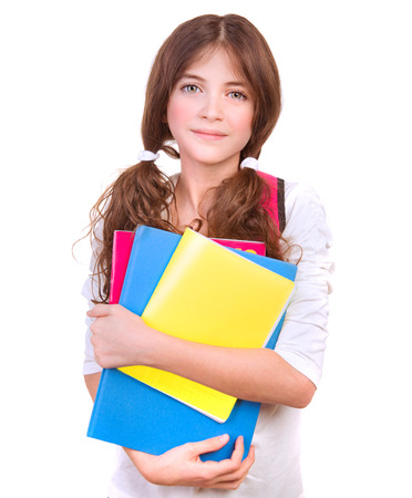 classbook: Portrait of cute brunette schoolgirl holding in hands three colorful notebooks, isolated on white background, back to school concept Stock Photo