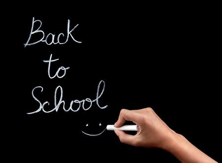 Woman hand writing on blackboard phrase :back to school, female body part, start of educational season concept photo