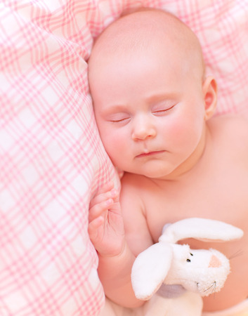 Cute baby asleep in pink bedroom, relaxing in the bed, adorable healthy child dreaming, safe childhood concept photo