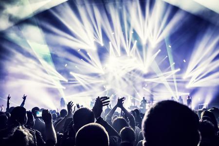 Menigte geniet van concert, gelukkige mensen springen, grote groep viert nieuwe jaar vakantie, partij achtergrond leuk concept Stockfoto