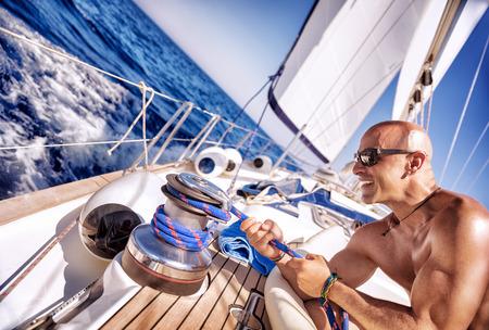 Knappe sterke man aan het werk op zeilboot, zeeman geniet plicht bemanning, luxe vakanties, yachting sport activiteiten, zeilen op de oceanen, de zomer vakantie en recreatie Stockfoto
