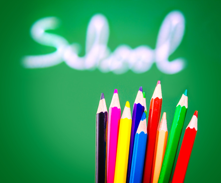 word lesson: Colorful pencils on green chalkboard background, soft focus of handwriting word, lesson of art, back to school concept