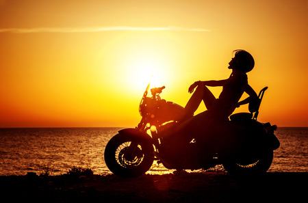 Woman biker enjoying sunset, female riding motorcycle, motorbike driver traveling the world, girl resting on the beach road, freedom lifestyle photo