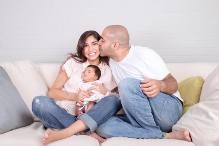 Handsome junge Vater küsst schöne lächelnde Mutter mit nettem neugeborenem Kind auf Händen, die Spaß zusammen zu Hause, liebevolle Familie Konzept Standard-Bild - 31560991