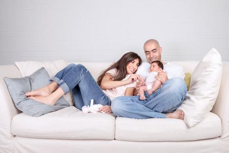 Jonge ouders met kleine baby thuis, zittend op de gezellige divan, genieten van familie, liefdevolle koppel met pasgeboren dochter, positiviteit en leuk concept Stockfoto
