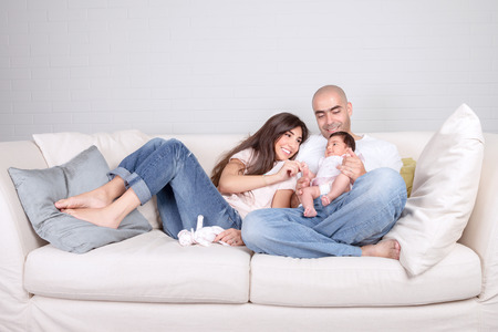 Young parents with little baby at home, sitting on cozy divan, enjoying family, loving couple with newborn daughter, positivity and fun concept