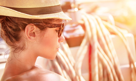 Closeup portrait of of cute female relaxing on the yacht in mild sunset light, side view of attractive woman wearing stylish hat and sunglasses, summer vacation concept photo