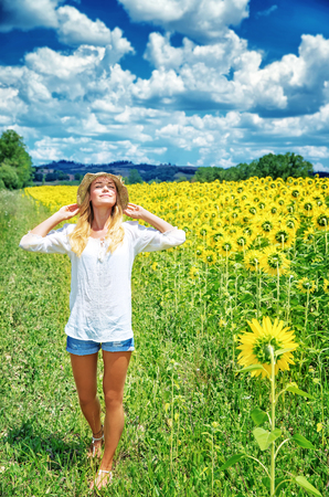 Joyful girl walking in sunflowers field, active lifestyle, agricultural landscape, enjoying blooming nature, autumn season concept  photo