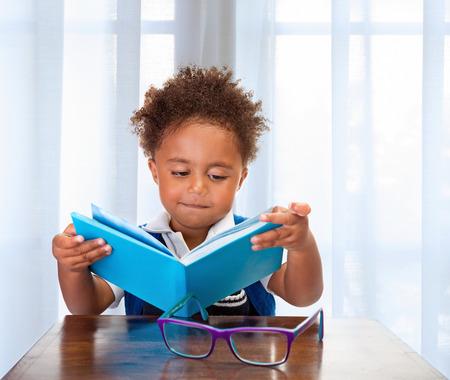 Malý školák četl knihu v učebně, rozkošný africké dítě učí lekci, dělat domácí úkoly, zpět do koncepce školy