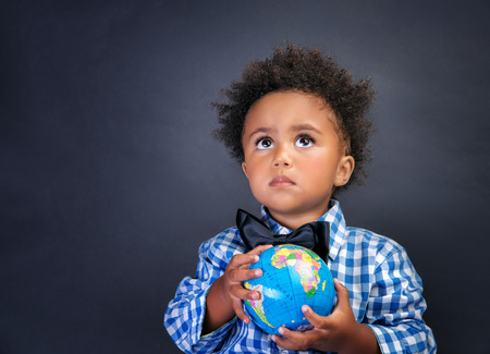 Portrait of cute little African boy holding in hands small globe on blackboard background, back to school concept 스톡 콘텐츠