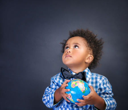 Portrait of cute little African boy holding in hands small globe on blackboard background, looking up, back to school concept