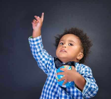 hand holding globe: Happy preschooler discovering world, african boy with raised up hand understand something and holding globe in another,  geography lesson, back to school concept
