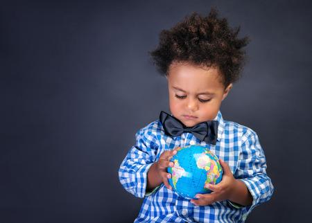 Glückliche Vorschulkind entdecken Welt, afrikanischer Junge, der auf kleine Welt, kopieren Raum, Geographiestunde, zurück zu Schulkonzept