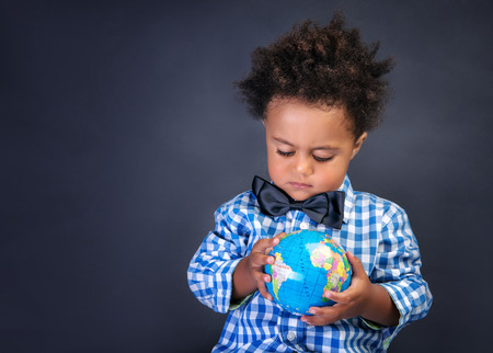 discovering: Happy preschooler discovering world, african boy looking on little globe, copy space, geography lesson, back to school concept