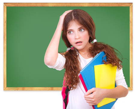 Portrait of confused school girl holding head by hand on green chalkboard background, didnt know answer on question, difficult test concept photo
