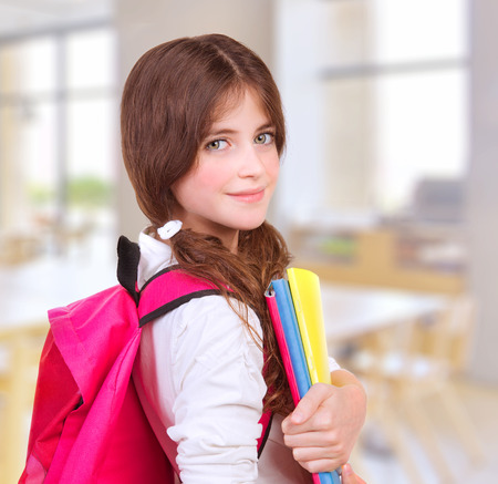 Side view of cute teen girl standing in classroom with colorful books in hands and bright pink backpack on shoulders, preparing to lesson, back to school, knowledge and education concept