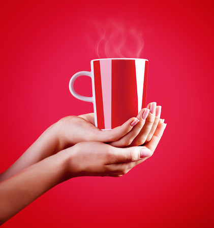 Close up on womans hands holding red cup of hot coffee isolated on red background, tasty hot drink, time for a break  Stock Photo