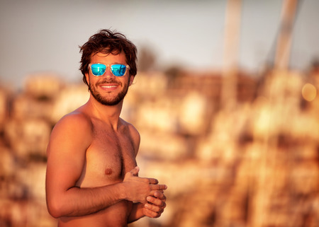 Portrait of handsome guy on the beach in mild yellow sunset light, perfect athletic body, summer vacation on luxury sailboat