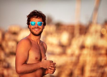 modelos posando: Retrato de chico guapo en la playa de suave luz del atardecer amarillo, cuerpo atl�tico perfecto, las vacaciones de verano en el yate de lujo