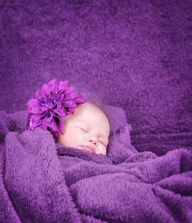 cintillos: Retrato de la pequeña muchacha con estilo recién nacido envuelto en una manta púrpura suave, vestido con accesorios de la flor de moda en la cabeza Foto de archivo