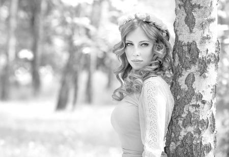 f�minit�: Portrait noir et blanc d'une femme attrayante posant dans le parc, portant des fleurs douces couronne, la mode et le concept de la f�minit� Banque d'images
