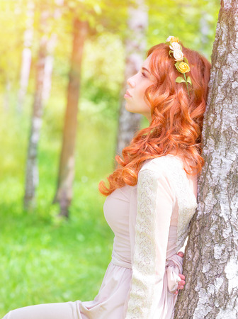 red hair woman: Side view of cute dreamy woman looking on the sun, enjoying warm sunny day, fashionable hairstyle, vogue and style concept