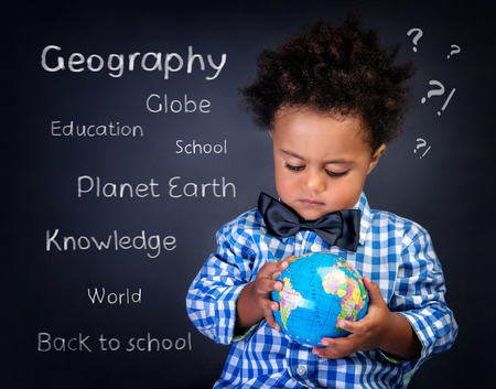 Closeup portrait of cute little African boy with small globe in hands, preparing to geography lesson, back to school concept photo
