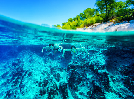 snorkelling: Happy active couple diving near beautiful tropical island, wearing snorkel and mask exploring sea bottom, summer vacation concept