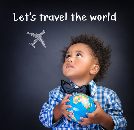 Portrait of little African schoolboy holding in hands small globe, dreaming about traveling all over the world, happy childhood concept photo
