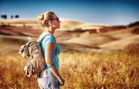 Turista lány élvezi kilátás gyönyörű száraz arany búza dombok mentén haladva Európa őszi szezonban, aktív életmód koncepció