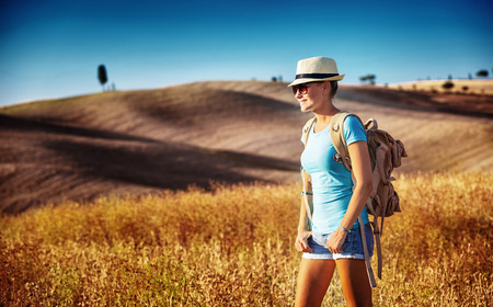 people travelling: Tourist girl enjoying view of beautiful dry golden wheat hills, traveling along Europe in autumnal season, active lifestyle concept   Stock Photo