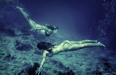 free diver: Two women synchronously swimming underwater, enjoying beauty of seabed, discovering marine life, active summer holidays, freedom concept
