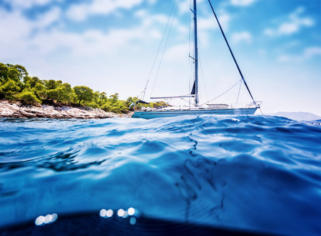 anchored: Luxury sailboat anchored near tropical island, amazing cruise along Greece, unforgettable summertime adventure, travel and tourism concept Stock Photo