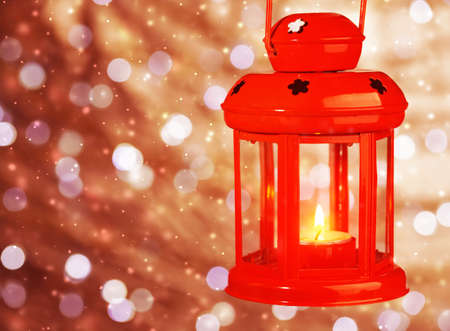 candle lights: Red antique Christmas lantern with burning candle inside hanging on bokeh blur background
