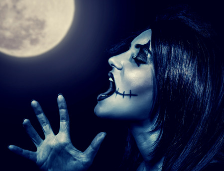 terrifying: Closeup portrait of terrifying witch yelling in full moon, aggressive woman with spooky makeup screaming in Halloween holiday  Stock Photo