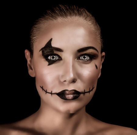 terrifying: Closeup portrait of terrifying witch with spooky painted face and torn mouth isolated on black background Stock Photo