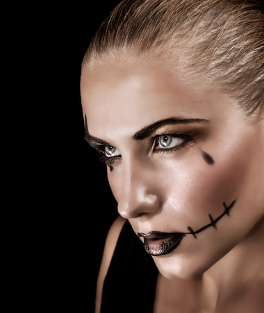 Portrait of aggressive young woman with creepy makeup and black tear isolated on black background photo
