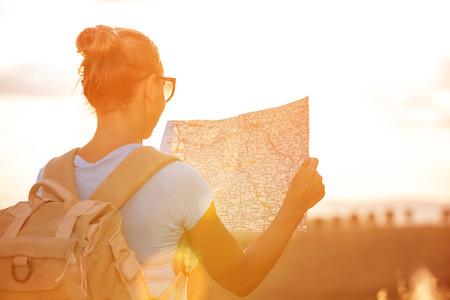 旅遊: 對旅行者的女孩背面尋找正確的方向在地圖上