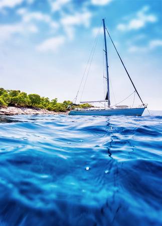 Luxury sailboat floating in the sea near tropical island photo