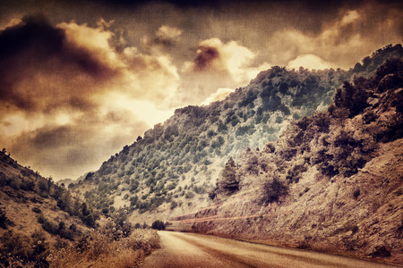 Grunge style photo of road passing between mountains photo
