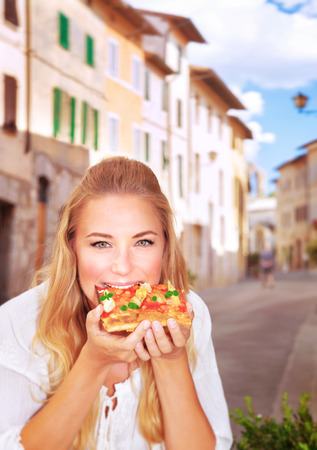 italy food: Portrait of cute girl sitting in outdoors restaurant and eating pizza, traditional Italian food, tasting European meal, travel and tourism concept