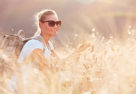 Portrait of cute happy traveler girl in dry ripe wheat field, looking away and enjoying beautiful agricultural view, autumn season photo