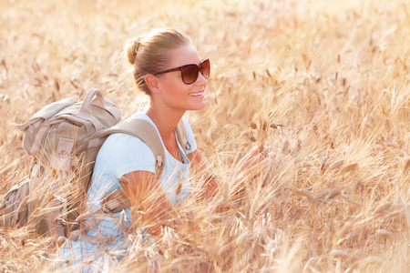 Happy cheerful woman sitting in beautiful golden wheat field, travel with backpack along Europe, active lifestyle concept photo