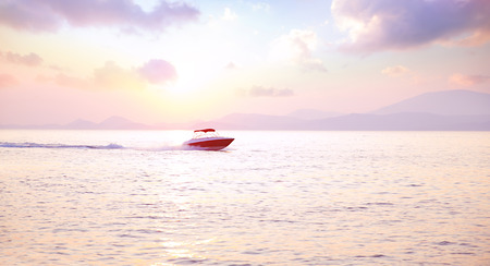 Luxury motorboat on the sea in mild pink sunset light