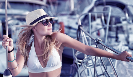 Portrait of attractive sexy woman tanning on the yacht, enjoying summer vacation in luxury sea cruise, freedom and enjoyment concept