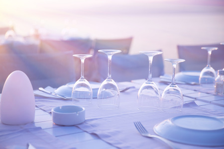 Beautiful table setting on the wedding, empty crystal wineglasses, expensive banquet on the beach, luxury outdoors restaurant